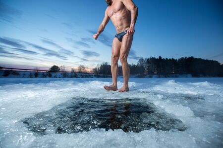 Photo pour Young man with beard stands barefoot on the ice after swimming in the winter lake - image libre de droit
