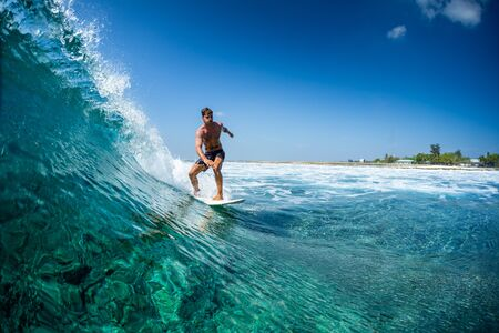 Photo for Surfer rides ocean wave in tropics - Royalty Free Image