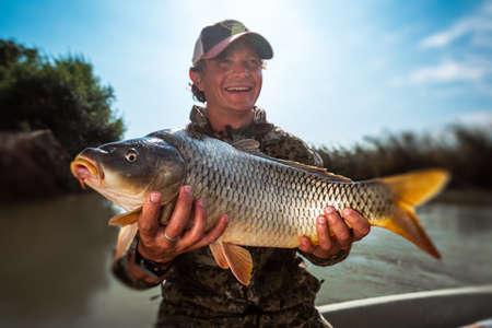 Photo pour Happy young fisherman holds the big Carp fish (Cyprinus carpio) and smiles - image libre de droit