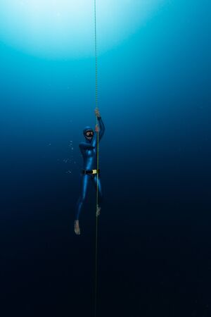 Photo pour Woman freediver holds the rope and hangs in the depth - image libre de droit