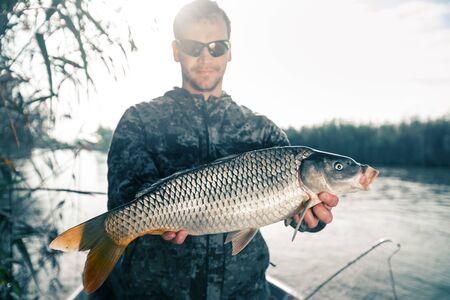 Photo pour Fisherman holds carp fish and looks at the camera - image libre de droit