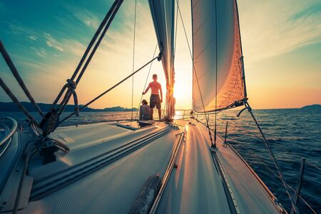 Photo for Young couple sailing on the boat at sunset - Royalty Free Image
