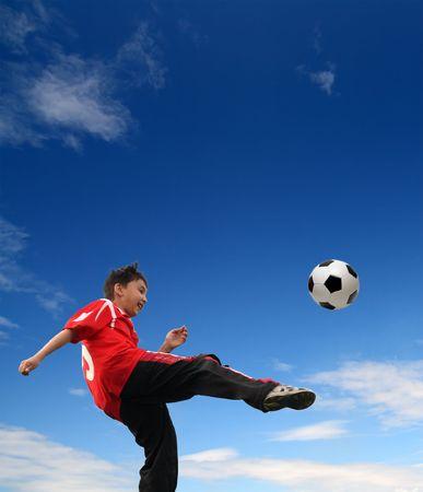 asian boy playing football under blue sky