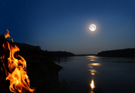 night landscape with bonfire and moonbeam in river