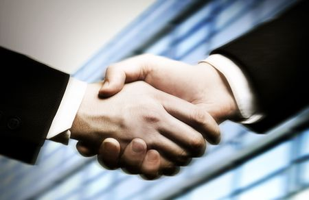 Foto de business hand shake and a office in background - Imagen libre de derechos