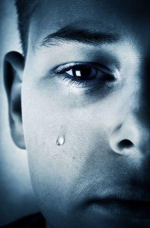 Sad face close-up - a tear is running down a cheek