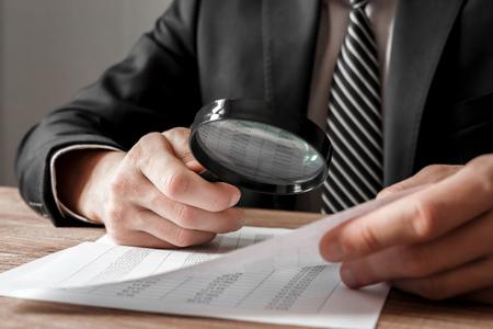 Foto de Businessman holding magnifying glass zoom and analyzing financial indicators - Imagen libre de derechos