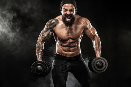 Foto de Muscular young fitness sports man workout with dumbbell in fitness gym - Imagen libre de derechos