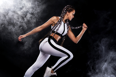 Foto de A strong athletic, woman sprinter, running on black background wearing in the sportswear, fitness and sport motivation. Runner concept with copy space. - Imagen libre de derechos