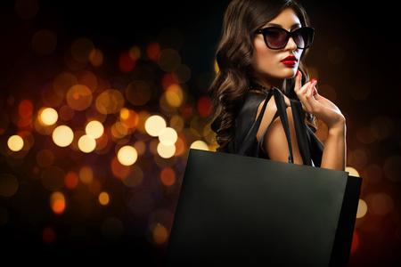 Foto de Black friday sale concept. Shopping woman holding grey bag isolated on dark background in holiday - Imagen libre de derechos