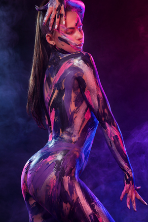 Photo pour Young woman painted different colors. Inspired dance to music. Body art colorful. An amazing woman with art fashion makeup and bodyart. - image libre de droit