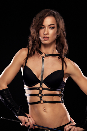 Sensual provocation of a sexy woman with whip on black background. BDSM concept