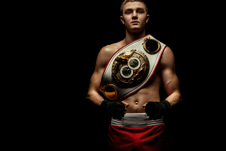 Foto de Sportsman, man boxer fighting in gloves with a championship belt. Isolated on black background with smoke. Copy Space. - Imagen libre de derechos
