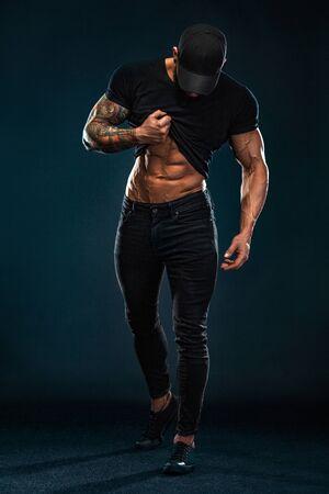 Foto de Strong and fit man bodybuilder shows abdominal muscles under a t-shirt. Sporty muscular guy athlete. Sport and fitness concept. Mens fashion. - Imagen libre de derechos