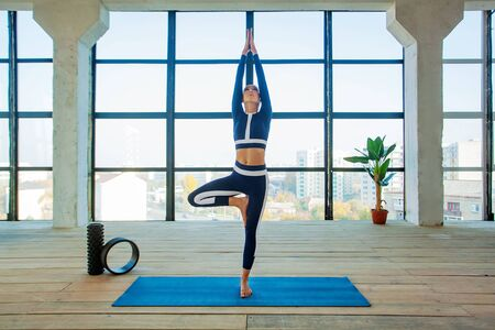 Yoga asana Indoor before a large panoramic window. Sports recreation. Beautiful young woman in yoga pose. Individual sports.