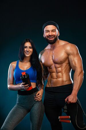 Photo for Athletic couple. Man and fit woman with sports equipment on dark background. - Royalty Free Image