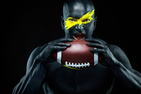 Photo pour American football fan with ball on black background. Fitness and sport motivation. Strong fit and athletic guy in body paint like a super hero. - image libre de droit
