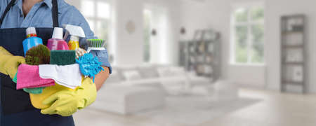 Photo pour Maid standing inside home holding a bucket fulfilled with chemicals and facilities for tidying - Web banner - image libre de droit