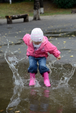 girl jumping in puddles