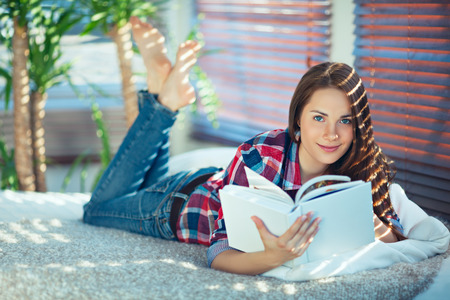 Photo pour Young pretty woman lying on her stomach and reading - image libre de droit