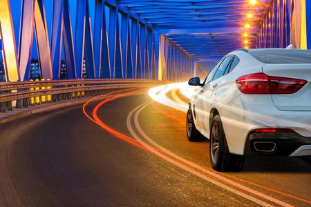Photo pour modern SUV driving across the bridge at night - image libre de droit