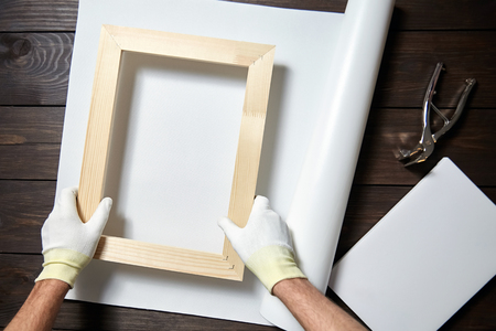 Photo pour Canvas stretching process. Wooden stretcher bar, canvas pliers, male hand in white protect gloves - image libre de droit