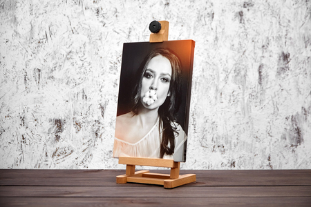 Photo pour Photography printed on canvas with gallery wrap. Portrait of a beautiful young woman. Wooden easel and stretched photo canvas - image libre de droit