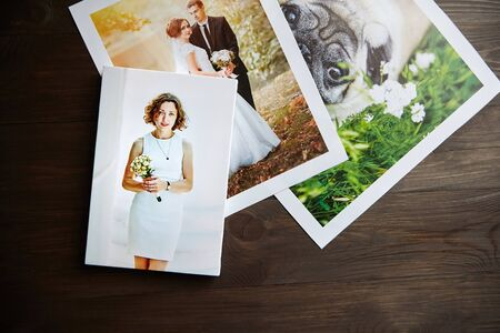 Foto de Photo canvas prints. Sample of stretched photography of woman with gallery wrap. Printed photos of a dog and a wedding couple lying on a wooden  table. Top view - Imagen libre de derechos