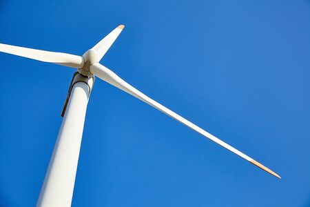 Photo pour Wind power turbine against a blue sky background. White blades of a wind generator closeup. Renewable energy source. Powerful and ecological green energy concept - image libre de droit