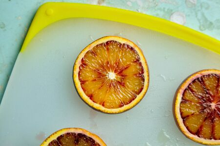 Photo pour Slice of blood or red orange fruit on cutting board, top view. Ripe citrus fruit with red juicy flesh - image libre de droit