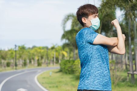 Photo pour Young male wearing medical mask and stretching his arms before workout training session at the park. Stay in fit during quarantine in the days of the Corona Virus or Covid-19 - image libre de droit
