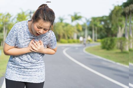 Exhausted female runner suffering painful angina pectoris or asthma breathing problems after training hard on summer. Running over training consequence.