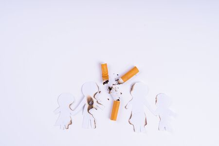 Photo pour Paper cut of family members destroyed by cigarette on white background. Smoking destroying family concept. Quit smoking for life on world tobacco day. - image libre de droit