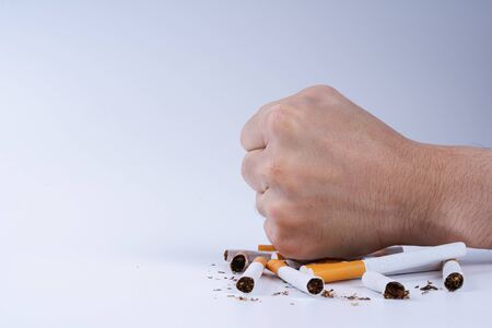 Photo pour Stop smoking. Close up of male hand breaking cigarette with his fist. Tobacco Day. Cigarette on white background. - image libre de droit