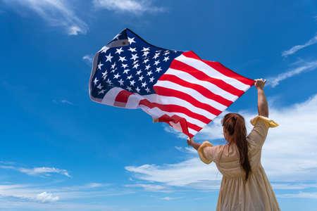 Photo pour woman standing and holding USA flag under blue sky. - image libre de droit