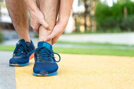 Foto de Male runner athlete leg injury and pain. Hands grab painful leg while running in the park. - Imagen libre de derechos