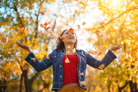 Portrait of a happy woman playing with autumn leaves in forest. autumn concept