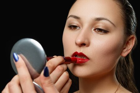 Foto de a young woman paints her lips with red lipstick on a black background. beauty photo, makeup, fashion - Imagen libre de derechos