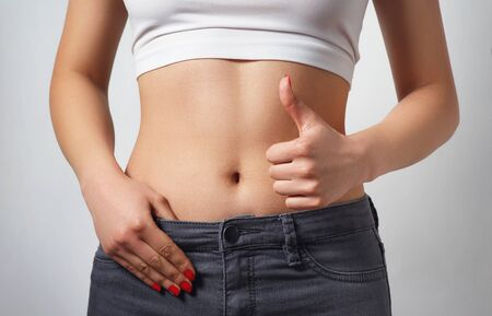 Photo pour slim, athletic waist of a young woman on white background. The hand in the foreground shows a finger up gesture. the concept of female beauty and health, nutrition and diet, a beautiful figure - image libre de droit