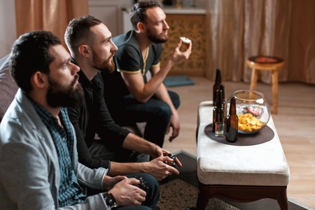 Men with a beard sitting on the couch at home with beer and chips with joysticks in hand playing computer video games. The concept of friendship, technology and weekend
