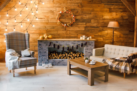 Foto de Home comfort. Armchair near the fireplace with firewood. Photo of interior of room with a wooden wall, wreath and garlands, Christmas atmosphere - Imagen libre de derechos