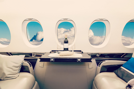 Photo pour Luxury interior in bright colors of genuine leather in the business jet, sky and clouds through the porthole - image libre de droit