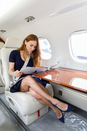 Foto de young beautiful woman in Luxury interior in bright colors of genuine leather in the business jet, sky and clouds through the porthole - Imagen libre de derechos