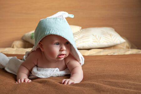 Photo for Adorable little baby lies on bed wrapped in white towel with hood - Royalty Free Image