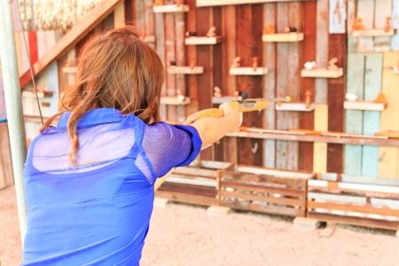 A woman playing shoot gun to doll