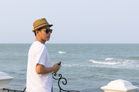 Smart and handsome asian man at sea background, sunset time, copy space.