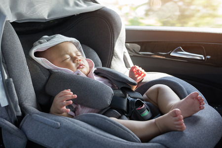 Photo pour Close Up Asian cute newborn baby sleeping in modern car seat. Child new born traveling safety on the road. Safe way to travel fastened seat belts in a vehicle with young kids. Trip with an infant. - image libre de droit