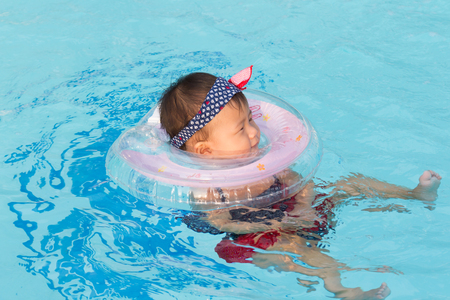 Asian cute eight month baby enjoy swimming pool, Active healthy first time playing swim in pool at home.