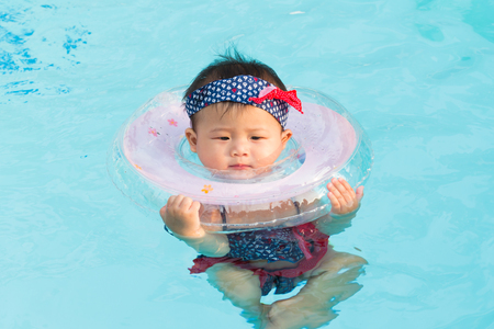 Asian cute eight month baby relax swimming pool, Active healthy first time playing swim in pool at home.
