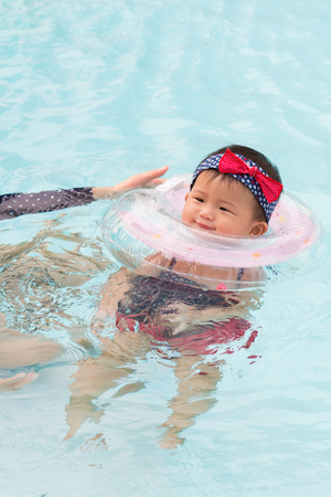 Asian young mother and cute eight month baby enjoying swimming pool, Active healthy first time playing swim in pool at home.